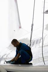 Engineer repairing wing of passenger jet in hangar