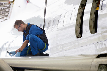 Engineer repairing wing of passenger jet in hangar