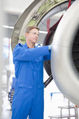 Engineer repairing engine on passenger jet in hangar