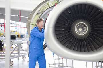 Engineer repairing engine on passenger jet in hangar