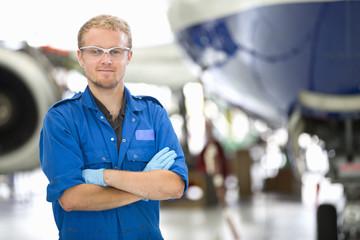 Portrait of engineer in front of passenger jet in hangar