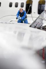 Engineer drilling into wing of passenger jet in hangar