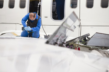 Engineer drilling into wing of passenger jet