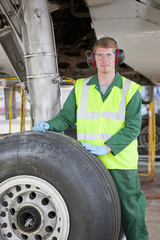 Engineer at landing gear wheel of passenger jet