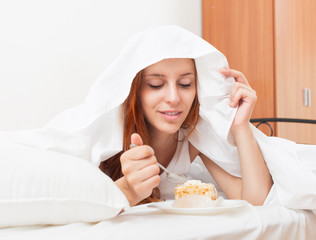Long-haired woman eating sweet cake under white sheet in bed