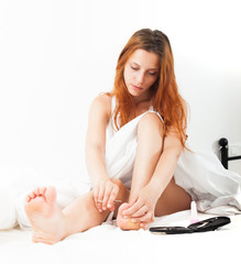 Young woman treats her toenails at home