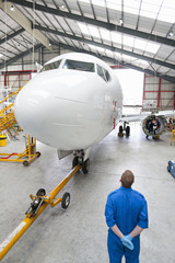 Engineer looking up at passenger jet in hangar