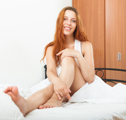 Red-haired woman waking in her bed with white sheets
