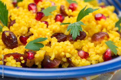 couscous with curry, dried cranberrie and herbs, selective focus