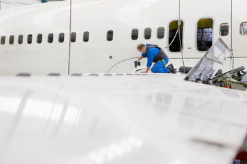 Engineer working on wing of passenger jet