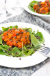 salad with arugula, black lentils and vegetable stew, close-up