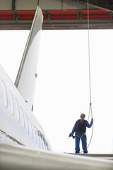 Engineer in harness next to passenger jet in hangar