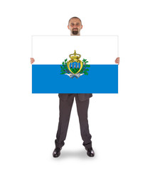 Smiling businessman holding a big card or flag