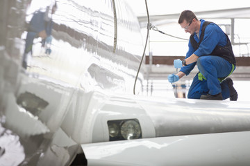 Engineer repairing wing on passenger jet in hangar