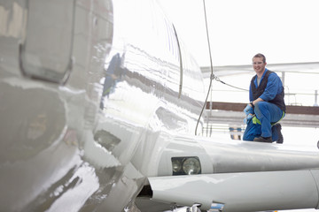 Portrait of engineer on wing of passenger jet