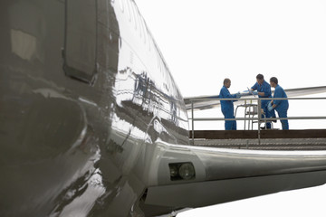 Engineers on scaffolding above wing of passenger jet