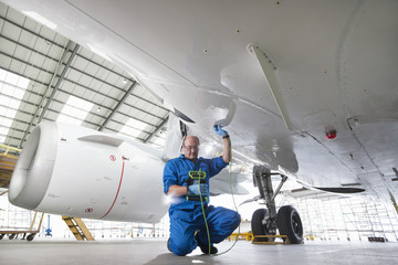 Engineer inspecting undercarriage of passenger jet in hangar
