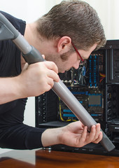 Man cleaning computer with hoover