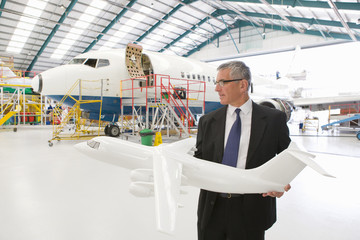 Businessman with model airplane and passenger jet in hangar