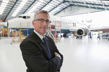 Businessman standing in hangar with passenger jet in background
