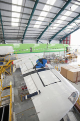 Engineer inspecting wing of passenger jet in hangar