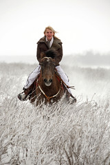 Attractive young blond woman riding a horse in the snow
