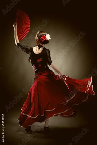 Leinwandbild Motiv young woman dancing flamenco on black