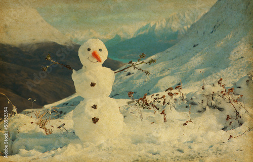 Happy snowman in mountains. Photo in retro style.