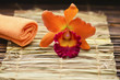 Spa Settings with orange towel with orchid on bamboo mat