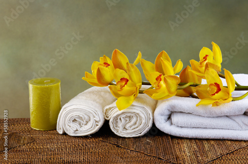 Spa setting with towel and candle, branch orchid