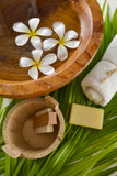 frangipani in wooden bowl of with soap ,towel and green leaves