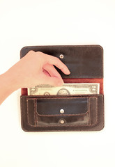 hand pulls money out of the black purse