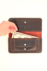 Hand pulling money out of a corner of the black purse