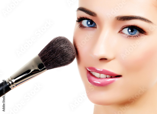 Pretty woman with a cosmetic brush, white background