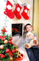 Boy near fireplace and christmas tree