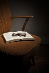Brille und Buch auf Cocktailsessel