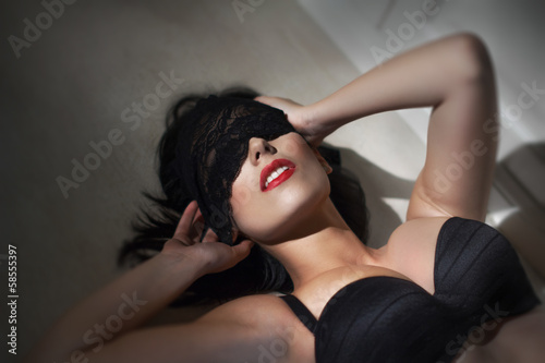 Young sexy woman with lace veil on eyes