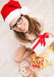 Beautiful girl in red Santa hat and eyeglasses holding xmas gift