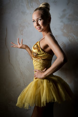 Lovely ballet dancer in yellow tutu posing indoors