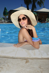 cute brunette in swimming pool with straw hat sunglasses