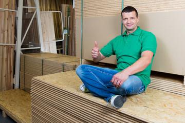 handwerker sitzt auf spanplatten