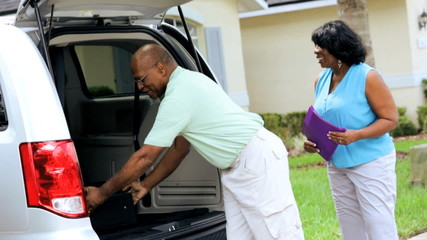 Retired Ethnic Couple Vacation Packing Suitcases Car