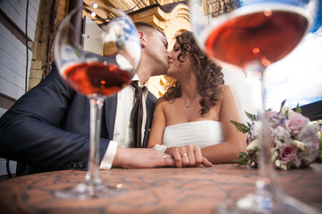 portrait through glasses of dating couple kissing in restaurant