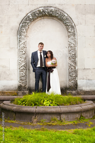 Portrait of low bride and tall groom posing in arch at park
