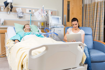 Woman Using Digital Tablet While Sitting By Patient