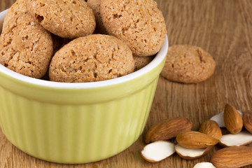 almond cookies in a ceramic dish with almonds