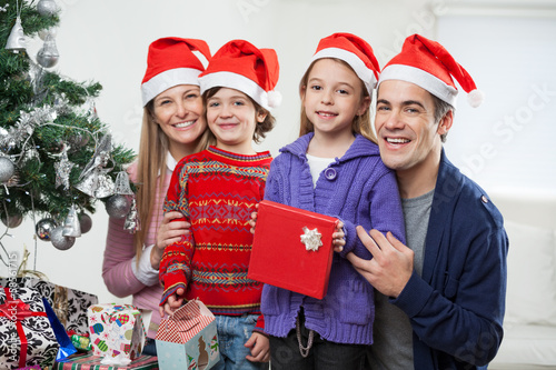 Family In Santa Hats With Christmas Present