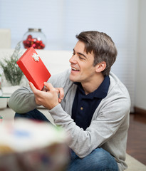 Smiling Man Looking At Christmas Gift