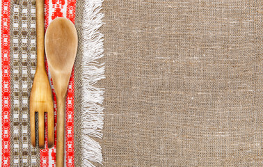 Burlap background bordered by country cloth and utensils