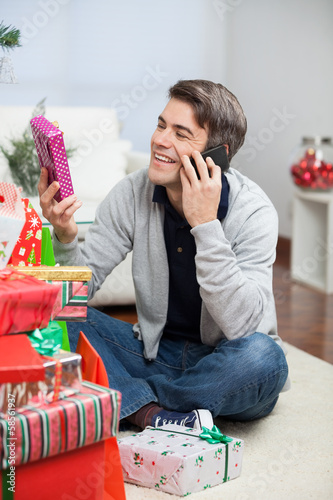 Man Holding Christmas Gift While Answering Mobilephone